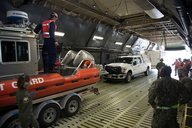 Members of the 349th Air Mobility Wing and 312th Airlift Squadron work with U.S. Coast Guard personnel to load and unload 25-foot (8 meter) Defender Class Response Boats Small (RB-S) aboard a C-5M Super Galaxy at Travis Air Force Base, Calif. (USAF Photo by Lt. Col. Robert Cousebaker)