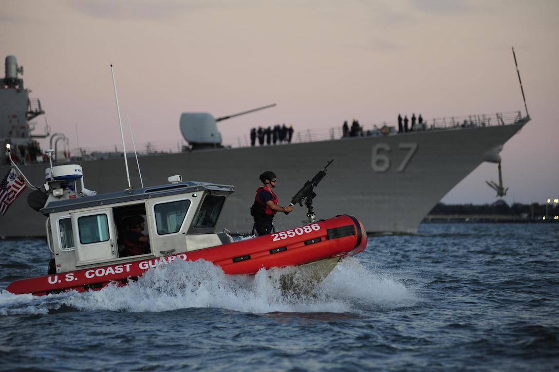 A Coast Guard Maritime Safety and Security Team crew, temporarily deployed from San Francisco, provides an escort for the USS Cole as the Navy destroyer returns to the Norfolk Naval Shipyard. Coast Guard crews worked to provide security zones for the Navy ships returning to harbor after Hurricane Irene. (U.S Coast Guard Photo by Petty Officer 3rd Class David Weydert)