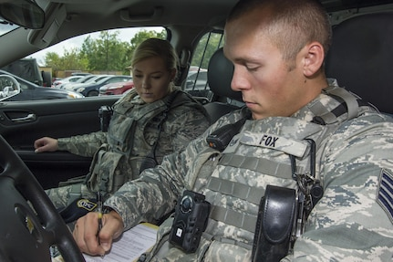 Staff Sgt. Sawyer Fox, right, and Airman 1st Class Sarah Shepherd, left, 11th Security Forces Squadron response force leaders, record information in a notebook during a patrol at Joint Base Andrews, Md., Oct. 4, 2016. JBA security forces defenders will be wearing the products for a period of six months as part of a test to determine which kind of camera to use throughout the Air Force. One of the main goals during the process is to disperse the new equipment information throughout the community to ensure they feel safe and aware. (U.S. Air Force photo by Senior Airman Jordyn Fetter)