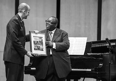Col. E. John Teichert, Joint Base Andrews and 11th Wing commander, presents Cyrus Chestnut, jazz pianist, a token of appreciation during a 2016 Jazz Heritage Series performance at the Rachel M. Schlesinger Concert Hall in Alexandria, Va., Oct. 21, 2016. Each year, a Jazz Heritage Series performance features a legendary icon of jazz. Chestnut has worked with many big bands, including the Lincoln Center Jazz Orchestra and the Dizzy Gillespie All-Star Big Band. (U.S. Air Force photo by Airman Gabrielle Spalding)