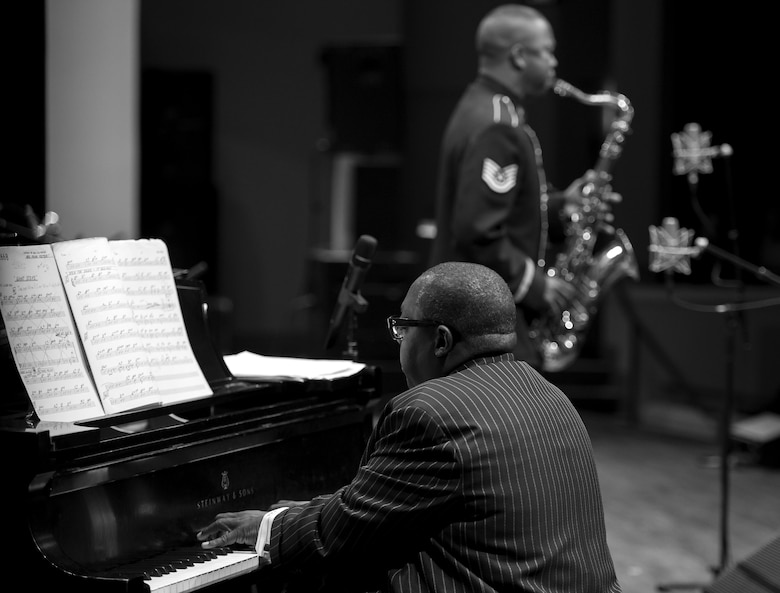Cyrus Chestnut, jazz pianist, plays the piano alongside Tech. Sgt. Grant Langford, U.S. Air Force Band's Airmen of Note tenor saxophonist, during the 2016 Jazz Heritage Series performance at the Rachel M. Schlesinger Concert Hall in Alexandria, Va., Oct. 21, 2016. Chestnut, who has worked with many big bands, including the Lincoln Center Jazz Orchestra and the Dizzy Gillespie All-Star Big Band, was the featured guest during this series performance. The Airmen of Note established the Jazz Heritage Series in 1990 and each year they perform with legendary icons of jazz. (U.S. Air Force photo by Airman Gabrielle Spalding)