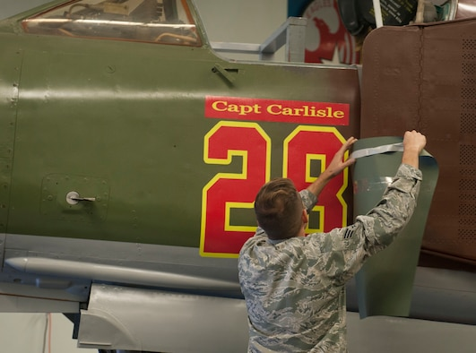 "An Airman reveals the nickname of a MiG-23 during a dedication ceremony at the Threat Training Facility on Nellis Air Force Base, Nev., Oct. 17. The MiG-23 was dedicated to Gen. ""Hawk"" Carlisle, commander of Air Combat Command, in recognition of his time as the Chief of Weapons and Tactics and Flight Commander for the 4477th Test and Evaluation Squadron from 1986 to 1988."