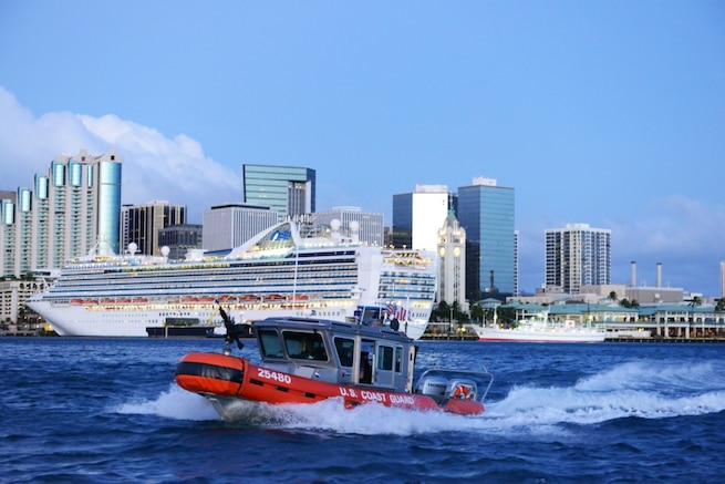 Crew members aboard a 25-foot Response Boat-Small from Maritime Safety and Security Team 91107 escort the cruise ship Pride of America out of Honolulu Harbor. The Coast Guard conducts escorts of high-capacity passenger vessels to ensure security of the passengers, the vessel and the port. (U.S. Coast Guard photo by Petty Officer 3rd Class Melissa E. McKenzie)