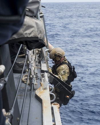 A Coast Guardsman assigned to the U.S. Coast Guard Tactical Law Enforcement Team South prepares to board a rigid-hull inflatable boat (RHIB) from the guided-missile destroyer USS William P. Lawrence (DDG 110). Providing a ready force supporting security and stability in the Indo-Asia Pacific, William P. Lawrence was operating as part of the John C. Stennis Strike Group and Great Green Fleet on a regularly scheduled 7th Fleet deployment. (U.S. Navy photo by Mass Communication Specialist 3rd Class Emiline L. M. Senn/Released)