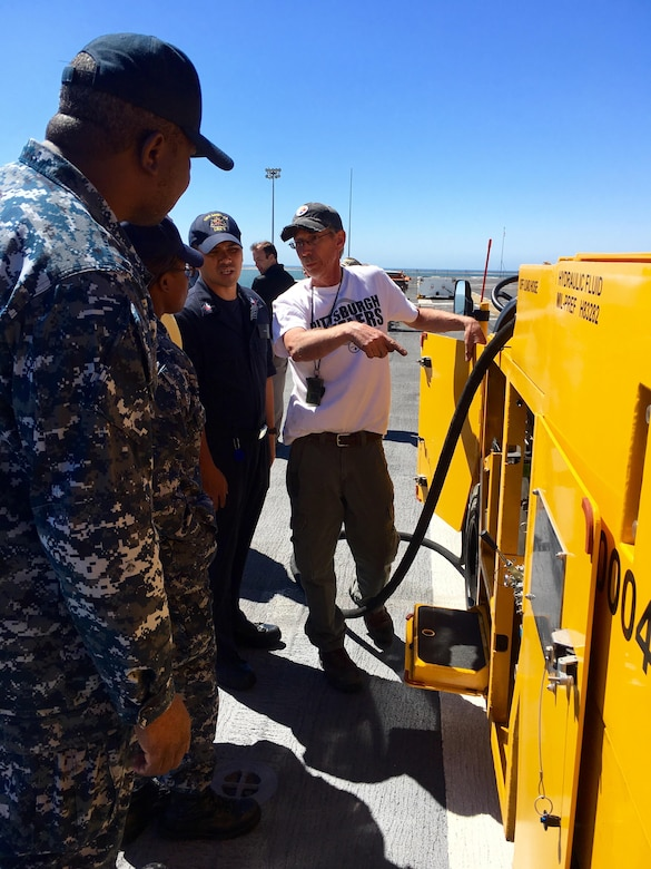 160915-N-IL267-007 SAN DIEGO (Sept. 15, 2016) Tracy Harasti, an environmental protection specialist with Naval Surface Warfare Center, Carderock Division, trains Seaman Uzoma Hojo in the use of the Mobile Cleaning Reclaim and Recovery System on the flight deck of the amphibious assault ship USS America (LHA 6). (U.S. Navy photo by Dustin Q. Diaz/Released)