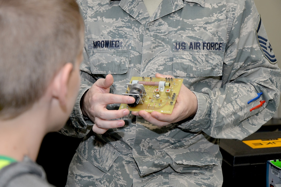 Master Sgt. Robert Mrowiec, 312th Training Squadron course development manager, demonstrates the makeup of a radio to a Wall Middle School student at Brandenburg Hall during a tour on Goodfellow Air Force Base, Texas, Oct. 24, 2016. Mrowiec explained that 312th TRS students are trained on how to make simple radios for use in emergencies. (U.S. Air Force photo by Airman 1st Class Randall Moose)