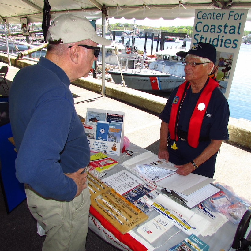 An Auxiliarist answers vessel safety  questions during the Safe Boating Day Open House at Coast Guard  Station Gloucester, Massachusetts. The annual event  draws hundreds of visitors interested in recreational boating safety.  May 21 – 27 is National Safe Boating Week and the launch of the Annual North American Safe Boating Campaign, a yearlong effort focused on spreading the message of boating safety and the critical importance of always wearing a life jacket each and every time on the water. (U.S. Coast Guard Auxiliary photo by: John W. Keyes)