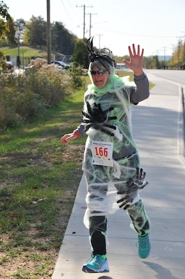 Leslie Mehall of the Defense Contract Audit Agency runs in her prize-winning spiderweb costume at the Monster Dash.