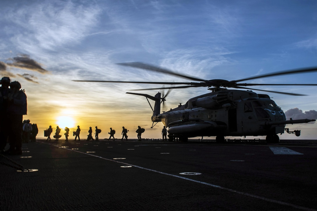 Marines depart a CH-53E Super Stallion aboard the USS Makin Island in the Pacific Ocean, Oct. 22, 2016. The amphibious assault ship is supporting the Navy's maritime strategy in the U.S. 3rd Fleet area of responsibility. The helicopter is assigned to Marine Medium Tiltrotor Squadron 163. Navy photo by Seaman Devin M. Langer