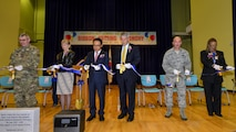 Key members of Team Osan, Department of Defense Education Activity and the local area cut a ribbon symbolizing the opening of the new Osan American Elementary School at Osan Air Base, Republic of Korea, Oct. 25, 2016. The ribbon cutting ceremony also included the students dedicating a time capsule, which will be buried in front of the new school until 2041. (U.S. Air Force photo by Senior Airman Victor J. Caputo)