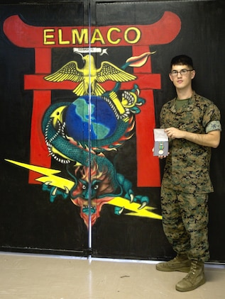 Cpl. Ricki D. Clement presents his Navy and Marine Corps Achievement medal he received for exceptional innovation at Camp Kinser, Okinawa, Japan, Oct. 20, 2016. Clement repaired a radio tester unit using a Vehicular Amplifier Unit, saving the Marine Corps nearly $64,000 in logistics and maintenance. Clement, from Houston, Texas, is a micro/miniature repair man with Electronics Maintenance Company, 3rd Maintenance Battalion, Combat Logistics Regiment 35, 3rd Marine Logistics Group, III Marine Expeditionary Force. (U.S. Marine Corps photo by Lance Cpl. Breanna Weisenberger/ Released)