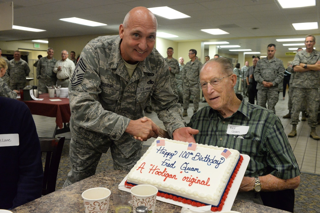 Chief Master Sgt. Kevin Muehler, the North Dakota Air National Guard state command chief, presents a birthday cake to charter member of the NDANG Fred Quam, a retired Chief Master Sergeant at the annual retiree breakfast Oct. 5, 2016. Quam turned 100 years old Oct. 2. He joined the North Dakota Air National Guard on the first day of the unit's existence, Jan. 17, 1947, and was in the Army Air Corp during WWII before that.(U.S. Air National Guard Photo by Senior Master Sgt. David H. Lipp)