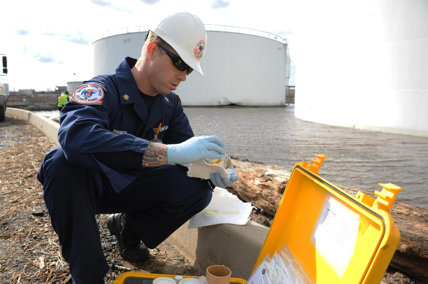 A Marine Science Technician with the Pacific Strike Team, takes a sample near a damaged tank that leaked during Hurricane Sandy at the Motiva Terminal in Sewaren, N.J. Responders are working to remove contained pockets of oil that leaked from the facility during Hurricane Sandy utilizing skimmers, vacuum trucks, absorbent pads and boom. (U.S. Coast Guard photo by Petty Officer 2nd Class Jaclyn Young)