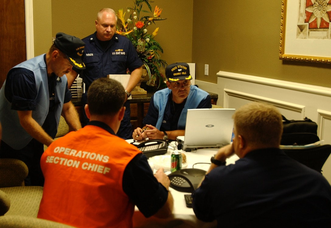 Coast Guard incident leaders discuss response plans at the incident command center. Coast Guard personnel are gathering information and initial damage reports from agency partners concerning Hurricane Katrina.  (U.S Coast Guard Photo by Petty Officer 3rd Class Robert Reed)