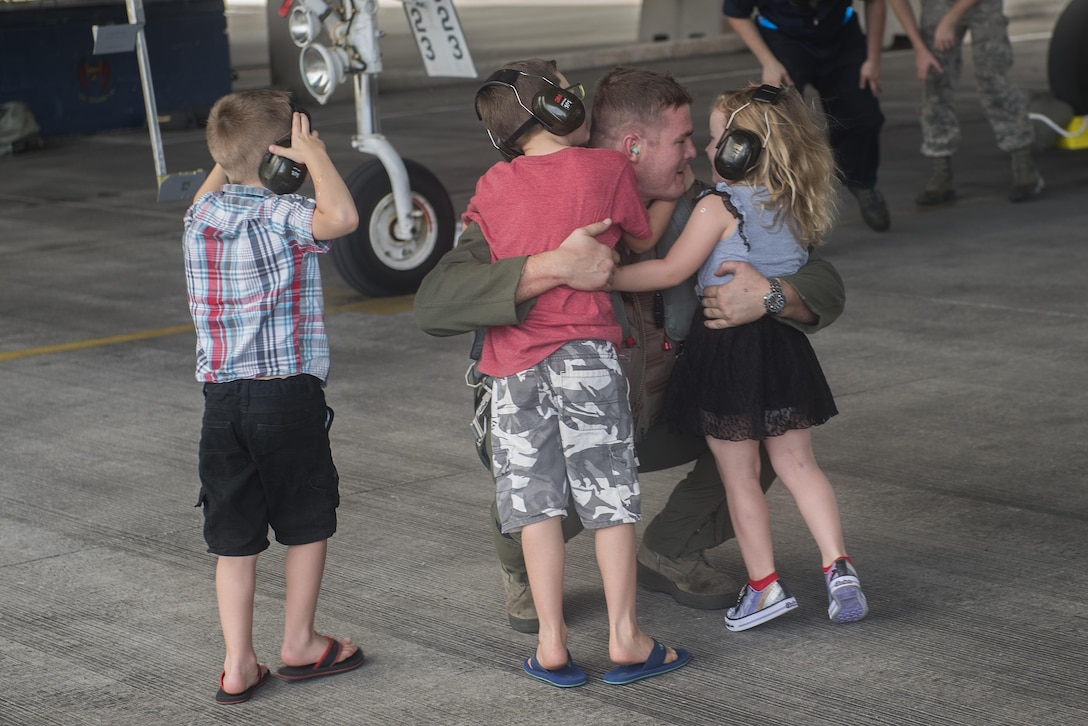 U.S. Air Force Capt. Tyson Hyer, 44th Fighter Squadron pilot, hugs his children after returning from training Oct. 26, 2016, at Kadena Air Base, Japan. The 44th FS spent more than three months training in exercises throughout the Indo-Asia Pacific region. (U.S. Air Force photo by Airman 1st Class Corey M. Pettis/Released)