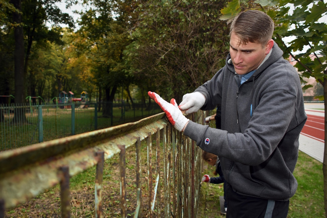 Staff Sgt. Gerry Rainwater, 86th Aircraft Maintenance Squadron electrician, prepares a fence to be painted at Elementary School No. Nine in Gniezno, Poland, Oct. 18, 2016. Rainwater was volunteering at the school while the 94th Airlift Wing, Dobbins Air Reserve Base, Georgia, and the 86th Airlift Wing, Ramstein Air Base, Germany, are working with the Polish air force during Aviation Detachment 17-1 in support of Operation Atlantic Resolve. (U.S. Air Force photo by Staff Sgt. Alan Abernethy)