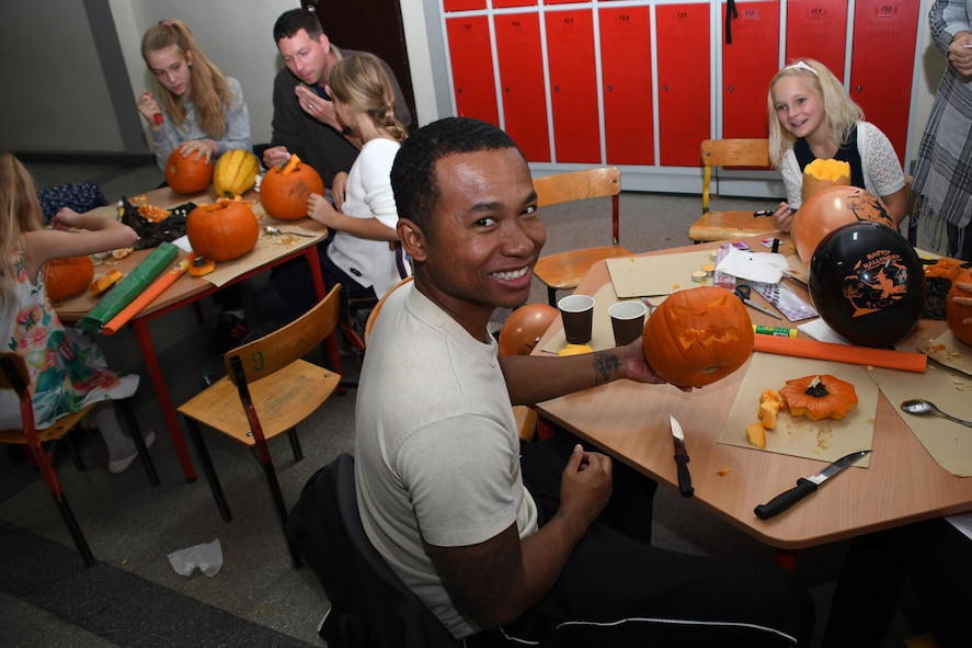 Senior Airman Arsenio Small, 86th Airlift Wing flight service center journeyman, and Staff Sgt. Michael Sterchi, 700th Airlift Squadron loadmaster, carve pumpkins with students at Elementary School No. Nine in Gniezno, Poland, Oct. 19, 2016. Pumpkin carving was one of several activities the Airmen participated in during a cultural orientation visit to the school while working with the Polish air force during Aviation Detachment 17-1 in support of Operation Atlantic Resolve. (U.S. Air Force photo by Staff Sgt. Alan Abernethy)