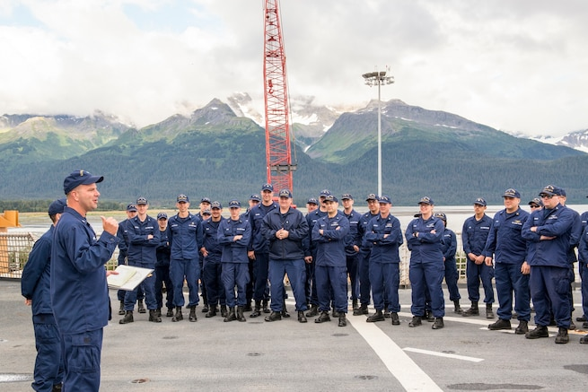 The Commander of the Cutter Healy addresses the crew during quarters on the flight deck in Seward, Alaska. Preparing for its second mission, the Cutter Healy embarked a team of researchers from the Scripps Institution of Oceanography, UC-San Diego, and the Office of Naval Research who are deploying an array of acoustic bottom moorings to collect data on how climate change and decreased ice coverage is affecting the Arctic Ocean. (U.S. Coast Guard photo by Petty Officer 2nd Class Christopher M. Yaw/Pacific Area External Affairs)