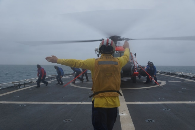 A Coast Guard Ensign signals the crew of a Coast Guard helicopter during a training