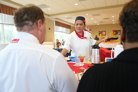 Violeta Smith, Courthouse Bay mess hall chef, presents her dish during the Chef of the Quarter competition at the Wallace Creek Mess Hall, Oct. 20. During the bi-annual event, four teams from various mess halls vied for the Chef of the Quarter Award and People's Choice Award. (U.S. Marine Corps photo by Cpl. Mark Watola /Released)