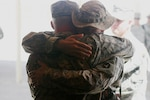 Soldiers with Able Company, 2nd Battalion, 136th Infantry Regiment, hug during a memorial ceremony held for Army Staff Sgt. Joshua R. Hanson in Taqaddum, Iraq, Sept. 4, 2006. Marine Corps photo by Lance Corporal Ryan L. Tomlinson