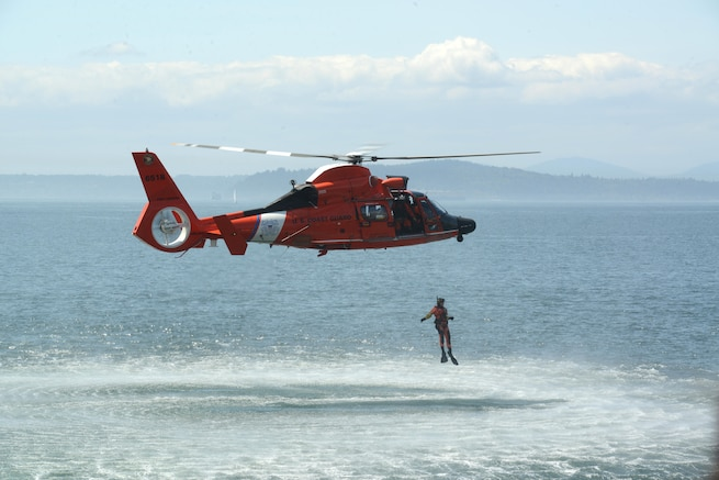A Coast Guard aircrew aboard an MH-65 Dolphin helicopter, from Air Station Port Angeles, Washington, performs a search and rescue demonstration on the Seattle waterfront during the Seafair Fleet Week. (U.S. Coast Guard photo by Petty Officer 1st Class Zac Crawford)