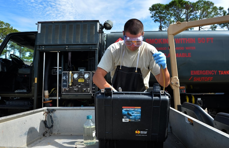 Staff Sgt. Timothy Andrews, NCO in charge of the fuels lab for the 1st Special Operations Logistics Readiness Squadron, collects fuel samples for testing at Hurlburt Field, Fla., Oct. 25, 2016. Fuel specialists test petroleum from fuel trucks monthly to ensure aircraft are provided clean gas. (U.S. Air Force photo by Senior Airman Andrea Posey)