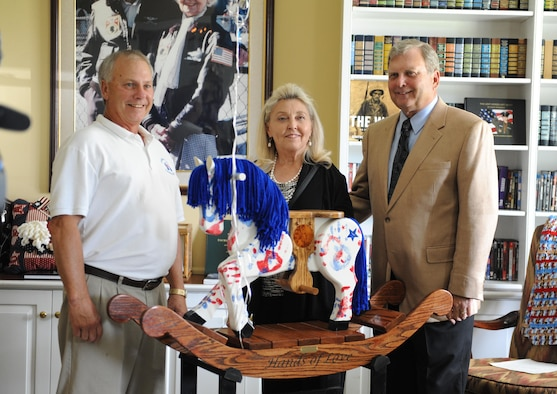 """Larry Vetter, 81st Medical Group Keesler Fisher House director; Susan Peterson, Keesler Fisher House Board member, and her husband, retired Lt. Gen. Mike Peterson pose for a photo with a """"Patriotic Pony"""" at the Keesler Fisher House during a dedication ceremony Oct. 24, 2016, on Keesler Air Force Base, Miss. Hero's Rock, a non-profit organization, dedicated the handmade pony in memory of 1st Lt. Michael Blassie, Jr., who was killed in action in Vietnam May 11, 1972. Since Sept. 1, 2016, Hero's Rock delivered 18 """"Patriotic Ponies"""" to 12 Fisher House locations; with Keesler being the final stop. The group created each pony in memory of a military member killed in action.  (U.S. Air Force photo by Kemberly Groue/Released)"""