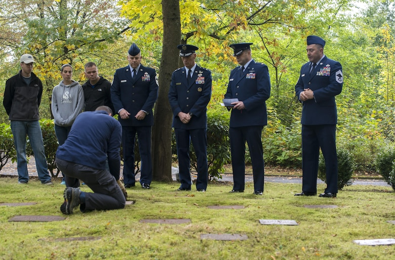 Lt. Col. Jason Shephard, 86th Operations Support Squadron commander, lays a gravestone in place during a dedication ceremony for Gary Currie, an infant who lost his life in 1952, at the American Kindergraves in Kaiserslautern, Germany, Oct. 15, 2016. Joy Caffey, Gary's mother, does not know where her son is laid to rest. Her family reached out to the Ramstein Area Chiefs' Group and they offered to dedicate a gravestone to Gary within the Kindergraves. (U.S. Air Force photo by Senior Airman Tryphena Mayhugh)
