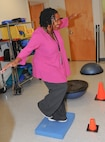 Lachaune Alexander, 78 Medical Group dental secretary, tries her balance during the Physical Therapy open house, Oct 26, 2016.To observe the National Physical Therapy month, 78th Med Group hosted an event with games to introduce their equipment. (U.S. Air Force photo by Misuzu Allen)