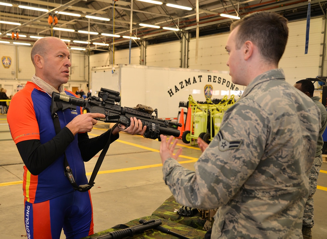 Wayne Harrod, left, amputee and retired British Army infantryman and long-distance cyclist, discusses military weapons with Airman 1st Class Kyle Reppucci, 100th Security Forces Squadron response force member, at the Steel Bones event Oct. 24, 2016, on RAF Mildenhall, England. Steel Bones is a local British organization similar to the Wounded Warrior Program, specifically aimed at amputees and their families. (U.S. Air Force photo by Karen Abeyasekere)