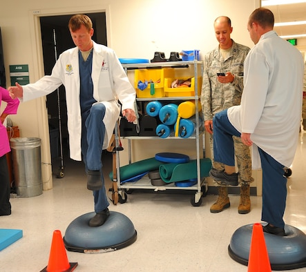 Captains Kyle Caldwell and Richard Waddell, both the 78th Medical Group dentists, stand on the balance trainer ball competition during the Physical Therapy open house, Oct 26, 2016. To obser the National Physical Therapy month, 78th Med Group hosted an open house on the second floor of the Medical Group facility. (U.S. Air Force photo by Misuzu Allen)