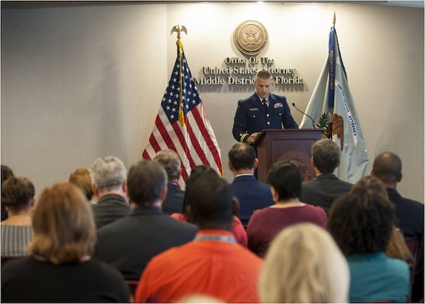 A Coast Guard public affairs officer, speaks to an audience during a ceremony at U.S. Attorney's Office Middle District of Florida where an interagency team received the Coast Guard Distinguished Public Service Award for their efforts to combat transnational criminal organizations involved in drug trafficking. (U.S. Coast Guard Photo by Petty Officer 1st Class Michael De Nyse)