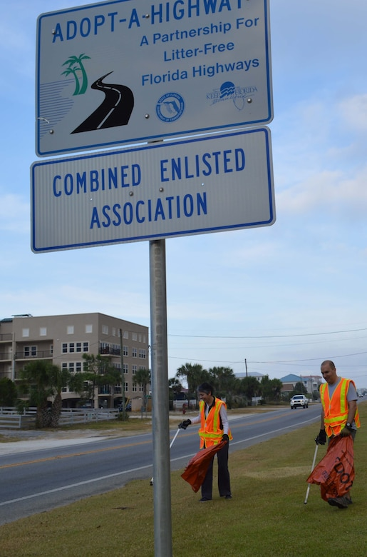 "Senior Master Sgt. Jaimie Saunders and Master Sgt. Albert Fouchy, Air Forces Northern Protocol office, begin picking up litter at one end of the AFNORTH CEA-sponsored portion of Highway 98 in Mexico Beach as part of the ""Adopt a Highway"" program. The signs, one at each end of a specific portion of road, provide a boundary marker for organizations participating in the program. (Air Force Photo by Mary McHale)"