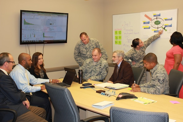 Brig. Gen. Cameron Holt, commander of the Air Force Installation Contracting Agency, visits a project team while they analyze Air Force spend using the Air Force Business Intelligence Tool and walk-through the Strategic Sourcing wheel. From left to right: Roger Westermeyer, Damon Roberts, Kristina Vineyard, Master Sgt. Michael Rankin, Gary Koenig, Senior Airman Jessica Carlton, Staff Sgt. Estephon Ramirez, and Saundra Scriven. (U.S. Air Force photo/Jennica Semon)