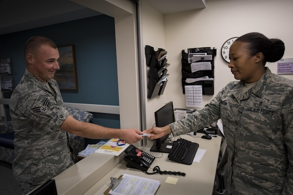 Master Sgt. Tracey McLendon, 23d Medical Support Squadron flight chief of diagnostic imaging, receives an identification card from Senior Airman Jeffrey Nelligan, 355th Medical Support Squadron diagnostic imagining technologist, Oct. 24, 2016, at Moody Air Force Base, Ga. The 23d MDSS radiology diagnostic imaging specialists use sophisticated technology to capture images of the human body to assist physicians in diagnosing patients quickly and accurately. (U.S. Air Force photo by Airman 1st Class Daniel Snider)