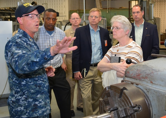 Chief Petty Officer Jason Broenneke explains how Sailors at Southeast Regional Maintenance Center (SERMC) use a metal lathe to create replacement parts for ship repairs to (from L to R) Lt. Col. Al Warthen, USMC, CAPT Dave Gombas, Mr. Craig Collier, Ms. Vickie Plunkett and Mr. Andrew Warren who are professional staff members on the House Armed Services Committee. The delegation was on Mayport to engage key staff on ship maintenance and workload. (Photo by Scott Curtis)