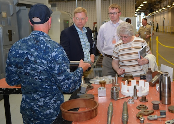 Chief Petty Officer Jason Broenneke shows examples of fabricated shipboard materiel created by Sailors at Southeast Regional Maintenance Center (SERMC) to (from L to R) Mr. Craig Collier and Ms. Vickie Plunkett who are professional staff members on the House Armed Services Committee. The staffers left with a better understanding regarding the different production lines, shops and labs present at SERMC. (Photo by Scott Curtis)