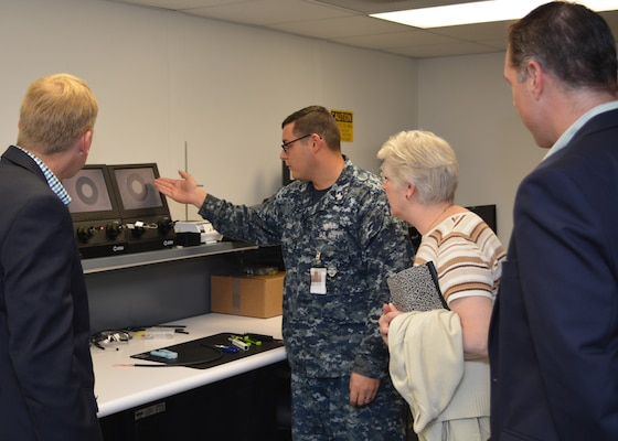 Petty Officer 1st Class Andrew Leigh (2nd from left) demonstrates to Mr. Craig Collier, (L) Ms. Vickie Plunkett and Mr. Andrew Warren who are professional staff members on the House Armed Services Committee, how Sailors at Southeast Regional Maintenance Center (SERMC) test, clean and repair fiber optic cable. The 2M (Miniature/Micro-miniature) shop at SERMC can inspect, repair, fabricate and troubleshoot fiber optic cable onboard all applicable classes of U.S. Navy surface ships. (Photo by Scott Curtis)