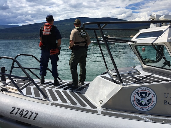 A Coast Guardsman surveys the waters alongside a U.S. Customs and Border Protection agent while conducting border patrol and law enforcement operations on Lake Koocanusa in Montana. This cooperative mission helps build better partnerships and training between the two agencies. (U.S. Coast Guard photo by Chief Warrant Officer Brian Hennessy)