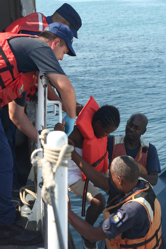 A boatswain's mate aboard the Coast Guard Cutter Tahoma, helps a Haitian migrant down to a small boat before being repatriated to Haiti. The crew of the Tahoma received the 88 Haitian nationals from the crew of the CGC Hamilton after they were rescued from a 50-foot sail freighter that was taking on water 45 miles north of Isle de Tortue, Haiti. U.S. Coast Guard photo by Petty Officer 3rd Class Bryan Bumstead. (U.S. Coast Guard photo by Petty Officer 3rd Class Bryan Bumstead)