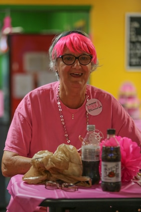 A guest watches her friends bowl during the Pink Bowling Night at Marine Corps Recruit Depot Parris Island Bowling Center Oct. 25. The guests dressed up in pink and bowled with pink bowling balls and prizes were won if a special pink pin was hit. The event was one of two for breast cancer awareness month.