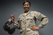 Lt. Col. Felicia Burks, the 92nd Medical Support Squadron commander, drops a pair of boxing gloves Oct. 21, 2016, at Fairchild Air Force Base, Wash. During her fight with cancer, Burks took up boxing as a way of staying physically fit. To her, the dropped gloves signify the end of her fight with cancer. (U.S. Air Force photo/Senior Airman Nick J. Daniello)