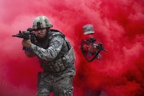 Airmen maneuver through concealing smoke during tactical combat casualty care training at Francis S. Gabreski Airport in Westhampton Beach, N.Y., Oct. 21, 2016. The airmen, assigned to the 106th Rescue Wing Security Forces Squadron, learned to react to enemy contact and attacks from improvised explosive devices while focusing on combat care. Air National Guard photo by Staff Sgt. Christopher S. Muncy.