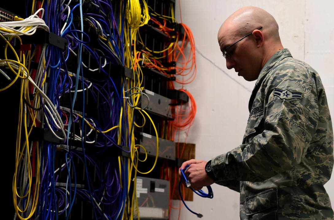 Airman 1st Class Michael De La Mater, 460th Space Communication Squadron network technician, changes out an Ethernet cable inside a communications closet Oct. 20, 2016, at Buckley Air Force Base, Colo. Each communications closet is used to house cables for all the computers within a designated area. (U.S. Air Force photo by Airman Holden S. Faul/ Released)