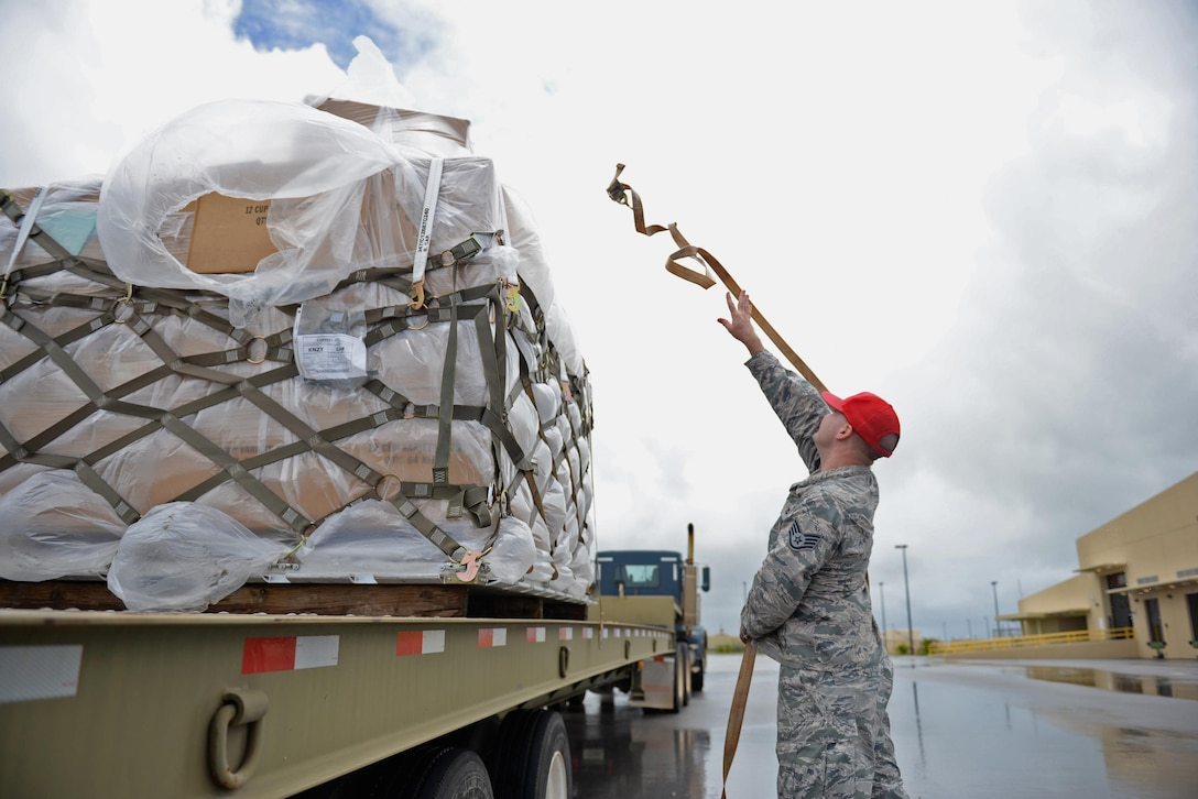Staff Sgt. Andrew Welch, 554th RED HORSE Squadron construction equipment operator, secures a pallet of coffee to a flatbed truck August 18, 2016, at Andersen Air Force Base, Guam. The 554th RHS supports the 36th Wing Chapel by transporting and storing coffee after it arrives on base. (U.S. Air Force photo by Airman 1st Class Jacob Skovo)