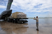 Senior Airman Dylan Cruson, 734th Air Mobility Squadron aircraft services technician, directs a Tunner 60K aircraft cargo loader as it backs away from a Boeing C-17 Globemaster III August 18, 2016, at Andersen Air Force Base, Guam. The assistance of the 734th AMS enabled the 36th Wing Chapel to efficiently distribute a large amount of coffee to Andersen AFB, boosting morale and raising awareness to the Chaplain Corps mission. (U.S. Air Force photo by Airman 1st Class Jacob Skovo)