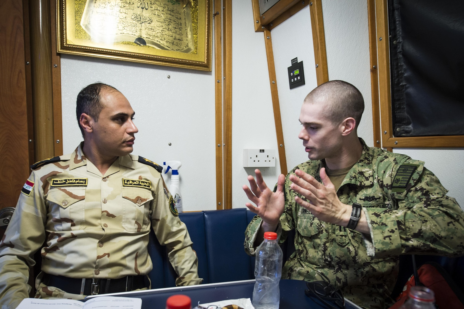 A U.S. Coast Guard Lt., assigned to Patrol Forces Southwest Asia (PATFORSWA), talks with commanding officer of the Iraqi Navy Swift Ship (P 302), before a Maritime Infrastructure Protection Exercise (MIPEX) between U.S. and Iraqi Navies, and U.S. Coast Guard. (U.S. Navy photo by Mass Communication Specialist 1st Class Benjamin A. Lewis/Released)