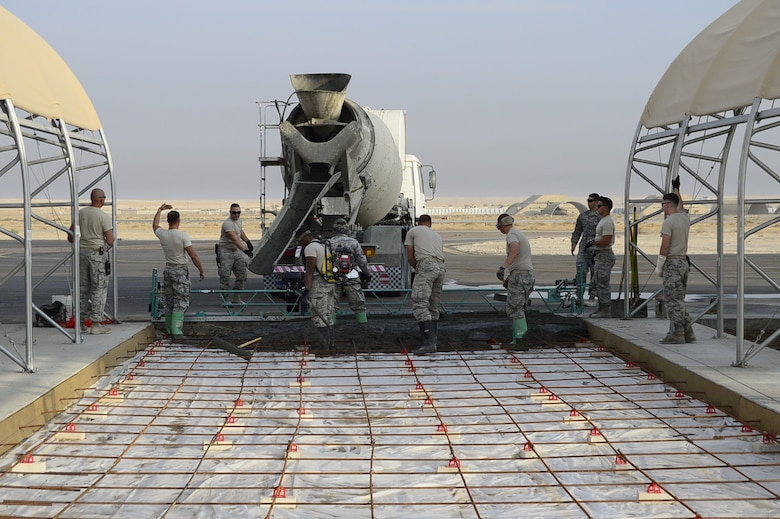 Airmen of the 386th Expeditionary Civil Engineering Squadron lay concrete on the flightline at an undisclosed location in Southwest Asia 24 Oct., 2016. The 386th ECES is expanding sunshades to prepare for an upcoming transition from MQ-1 Predators to MQ-9 Reapers. (U.S. Air Force photo by Capt. Casey Osborne/Released)