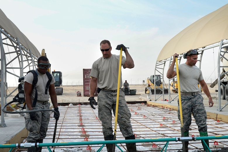 From left, Airman 1st Class Marco Small-Gonzalez, Staff Sgt. Cameron Kruell and Senior Airman Jon Martinez, 386th Expeditionary Civil Engineering Squadron pavements and equipment technicians, review their progress while smoothing out concrete at an undisclosed location in Southwest Asia 24 Oct., 2016. The 386th ECES is expanding sunshades to prepare for an upcoming transition from MQ-1 Predators to MQ-9 Reapers. (U.S. Air Force photo by Capt. Casey Osborne/Released)